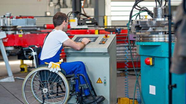 Ein Arbeitnehmer im Rollstuhl bedient eine Maschine.