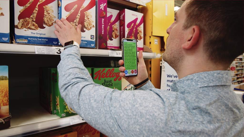 Mann scannt Cornflakes-Verpackung im Supermarkt.