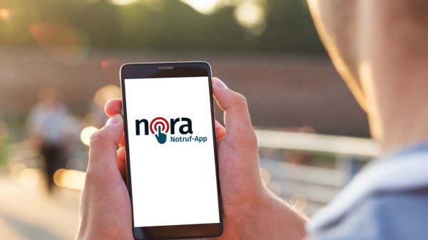 Mann hält ein Smartphone mit der Nora-App.