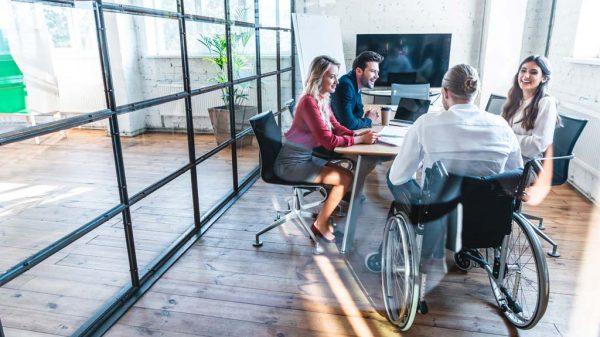 In einem Besprechungszimmer sitzen vier Menschen, darunter ein Mann im Rollstuhl.