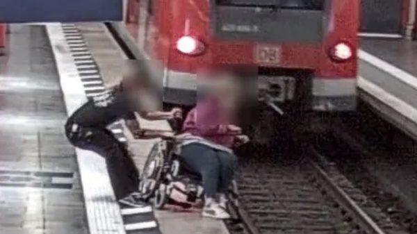 Foto aus der Überwachungskamera: Mann rettet Rollstuhlfahrerin vor Sturz in die Gleise (Foto: