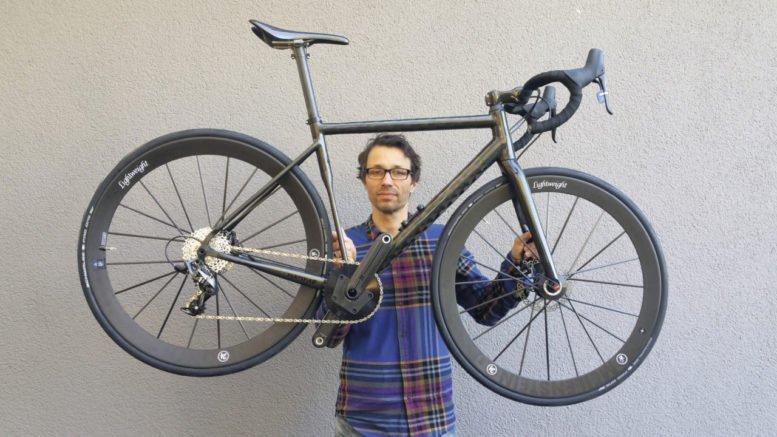 Marc Siebert hält ein Fahrrad in die Höhe.