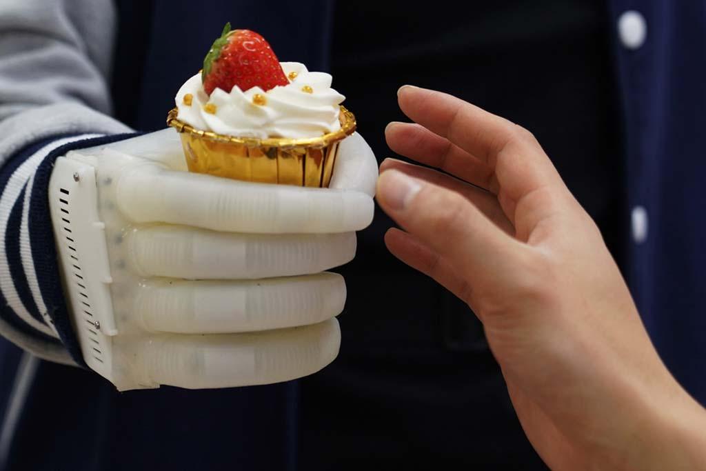 Aufblasbare Hand hält einen Cupcake.