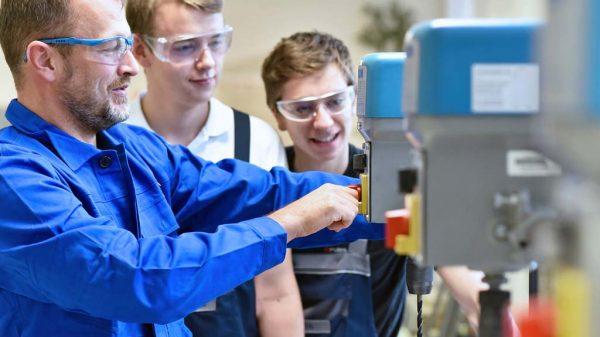 Zwei Elektrotechnik-Azubis sehen ihrem Ausbilder bei der Arbeit zu.