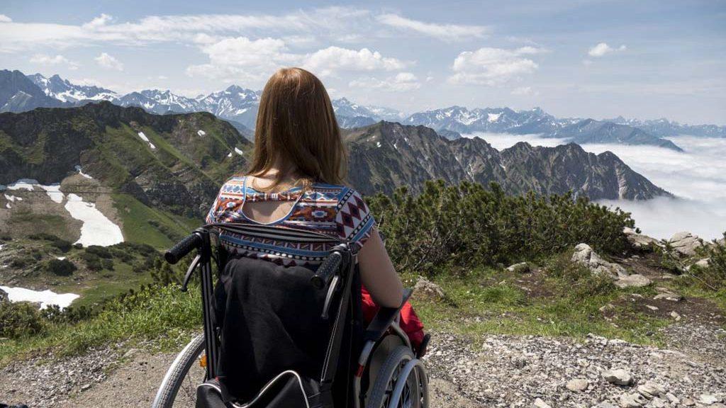 Frau im Rollstuhl betrachtet das Bergpanorama.
