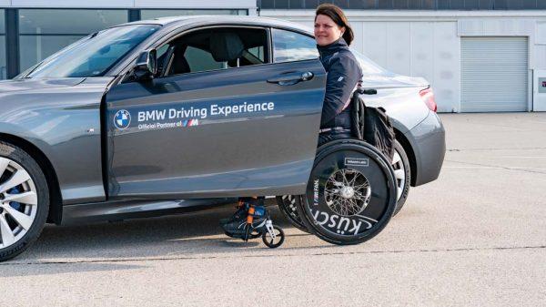Tina Schmidt-Kiend im Rollstuhl vor einem BMW