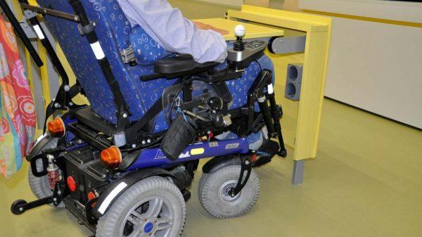 E-Rollstuhl an einem barrierefreien Sitzplatz im Vorlesungssaal.