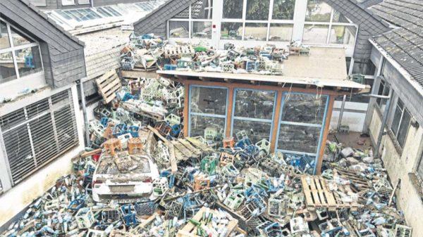 Außenansicht der zerstörten Einrichtung mit aufgetürmten Getränkekisten und Paletten.