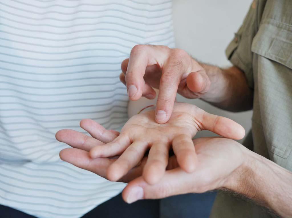 Ein Mann berührt mit seinem Finger Druckpunkte auf einer Kinderhand.