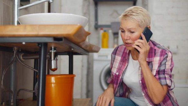 Frau kniet vor leckenden Waschbecken und telefoniert.