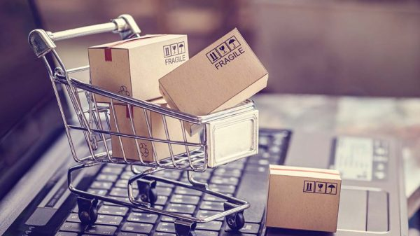 Beladener Spielzeug-Einkaufswagen auf einem Laptop.