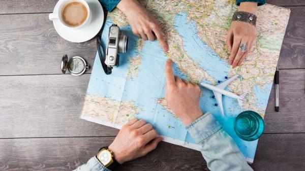Ein Paar plant ihre Reise anhand einer Landkarte.