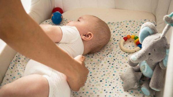 Die Mutter dreht ihr Baby im Kinderbettchen.