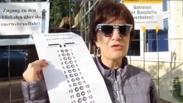 Silja Korn hält eine Wahlschablone in die Kamera.