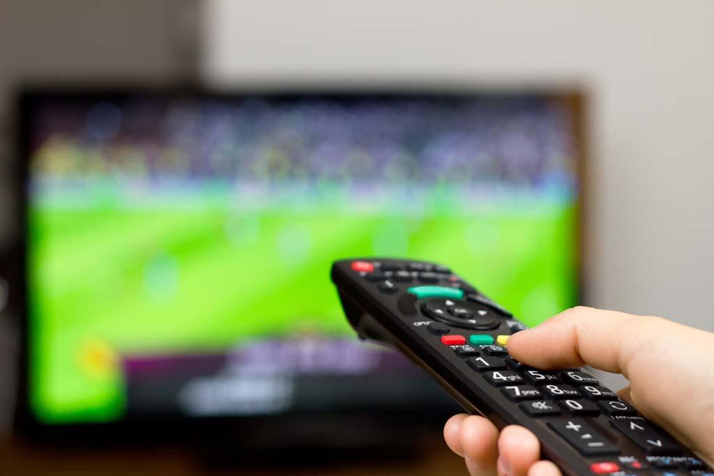 Mann schaut sich Sport im Fernseher an.