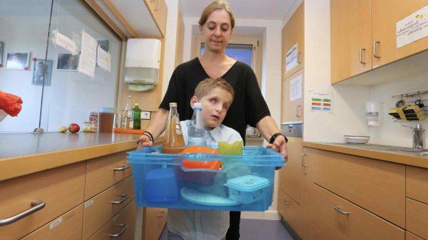 Seit seiner Geburt kann Lucas weder sehen noch hören. Hier trägt er gemeinsam mit einer Erzieherin der Wohneinrichtung, in der er lebt, das Frühstück zum Tisch.