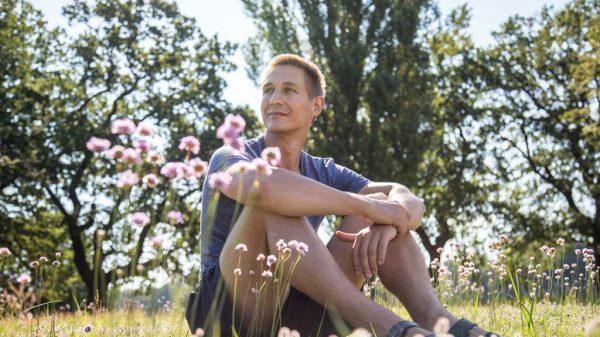 Mann sitzt entspannt in einer Blumenwiese.