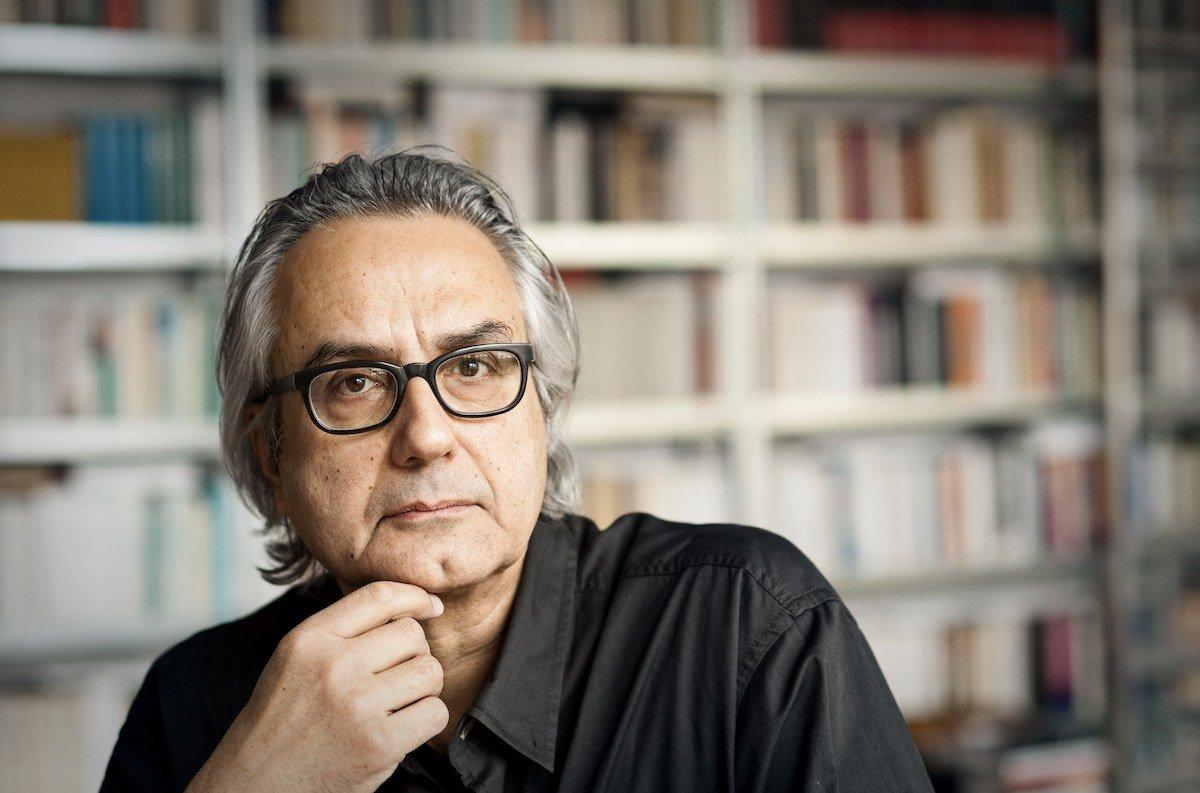 Porträt Friedrich Ani vor einem Bücherregal. Er hat einen Scheitel, graue Haare und eine Brille.