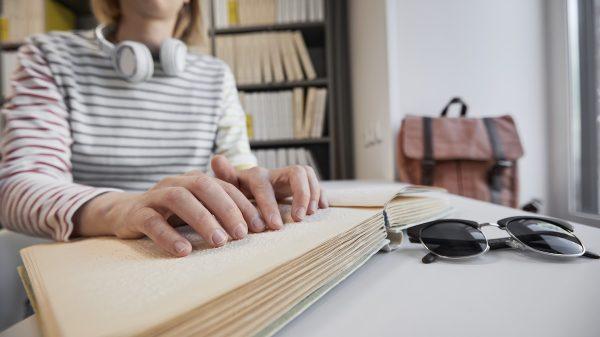 Eine blinde Frau liest ein Buch in Braille-Schrift