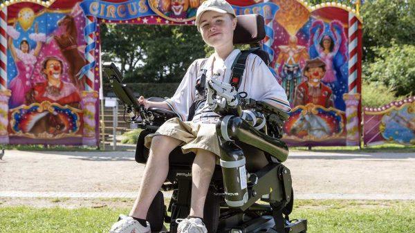 Carl Josef sitzt im E-Rollstuhl. Im Hintergrund ist ein bunter Zirkuseingang zu sehen.