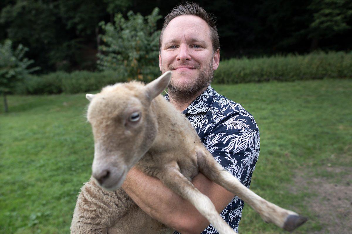 Christopher Brandenstein hält ein Schaf in die Kamera.