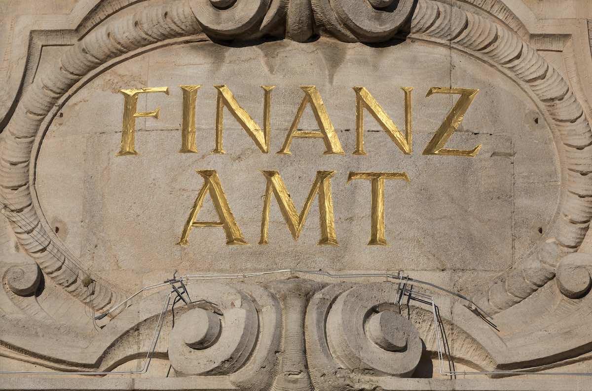 """Eine Sandsteinmauer mit der Aufschrift """"Finanzamt"""" in goldfarbenen Buchstaben."""