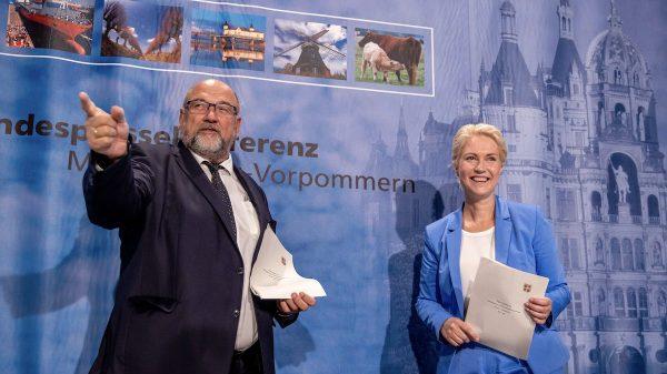 Harry Glawe steht links und zeigt mit seinem Finger in eine Richtung, während rechts von ihm Manuela Schwesig steht. Er trägt einen dunklen Anzug und eine Krawatte, sie einen blauen Blazer und eine blaue Stoffhose.