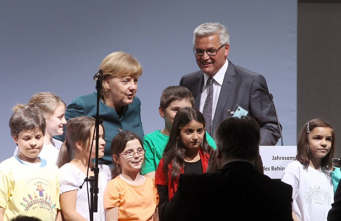 Merkel und Hüppe stehen zusammen mit einer Kindergruppe.