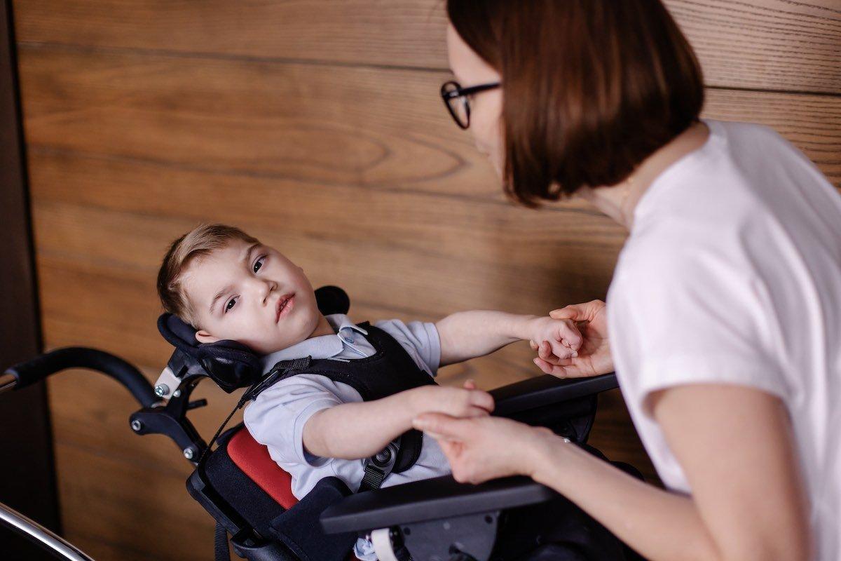 Ein Kleinkind im Rollstuhl schaut in die Kamera, während seine Mutter es an den Händen hält.