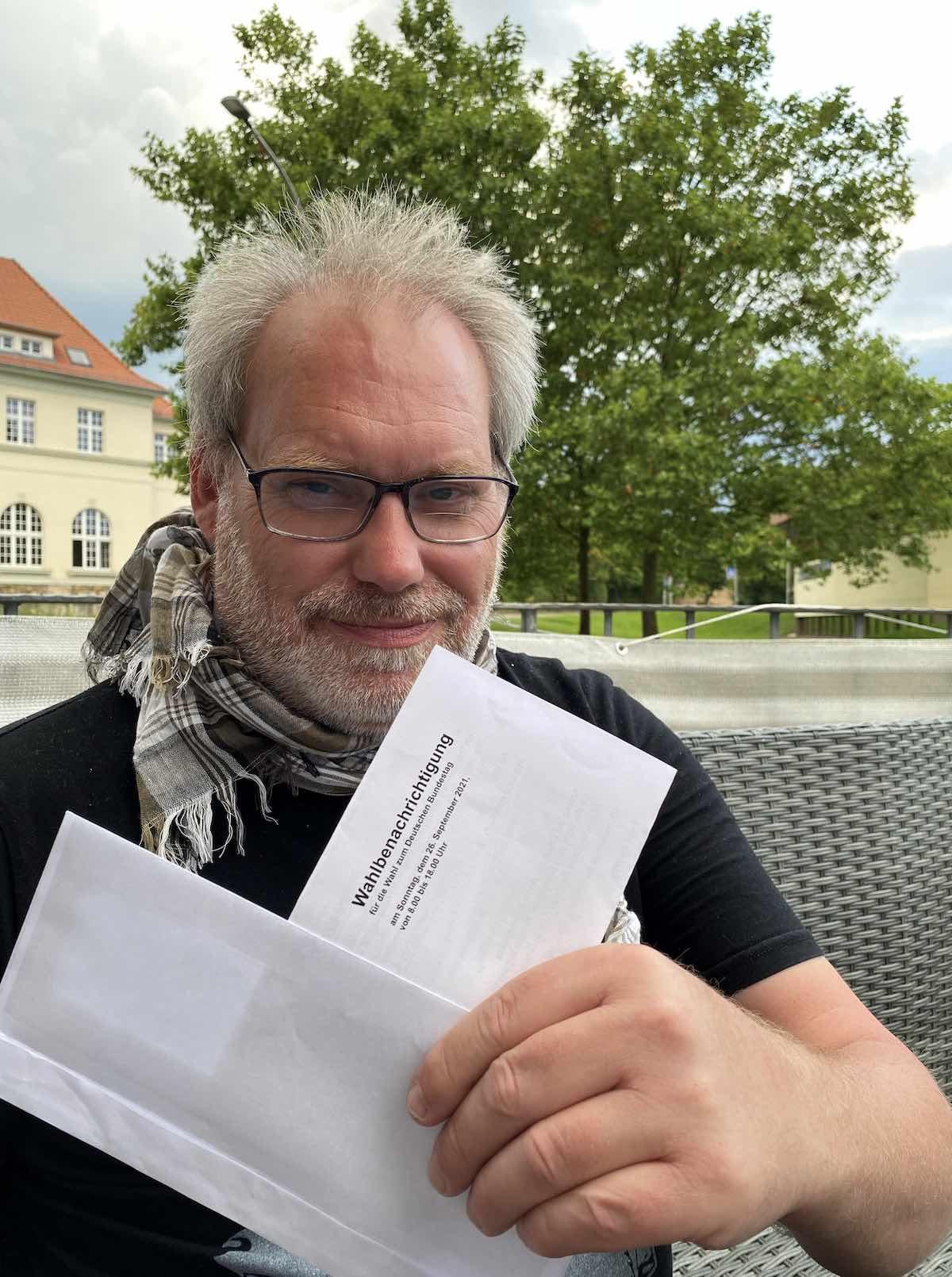 Klaus Winkel mit der Wahlbenachrichtigung, die er erhalten hat. Er trägt eine Lesebrille, ein Schal und ein T-Shirt.