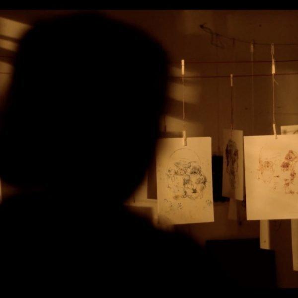 In einem dunklen Zimmer hängen viele Porträtzeichnung an Wäscheleinen. Im Vordergrund sieht man die Umrisse eines Kopfes.