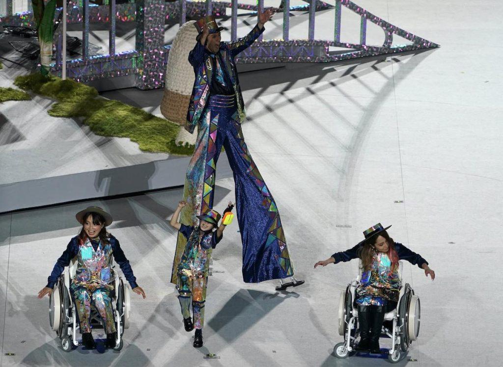 Zwei Rollstuhlfahrerinnen, eine gehbehinderte Frau und ein Riese auf Stelzen bei der Darbietung.
