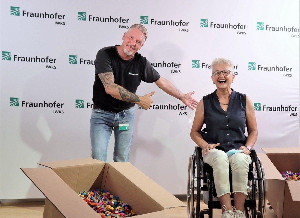 Thomas Windhagen (links), zeigt mit erhobenem Daumen auf die im Rollstuhl sitzende Rita Ebel (rechts), die freudig lacht. Vorne sind zwei Kisten mit kleinen, bunten Bausteinen zu sehen, im Hintergrund eine Wand, bedruckt mit zahlreichen Logos des Fraunhofer IWKS.