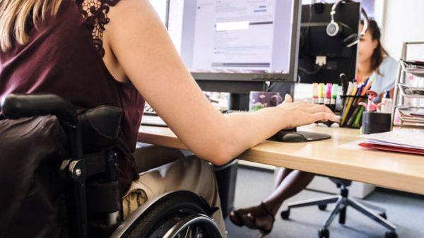 Rollstuhlfahrerin in einem Büro und an einem Computer.