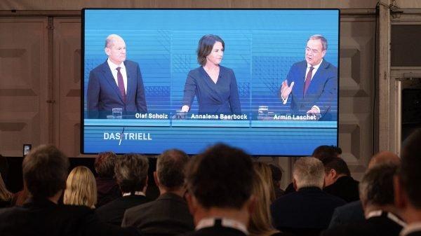 Bei einem Public Viewing in Berlin zeigt ein großer Fernsehschirm die Politiker Olaf Scholz, Annalena Baerbock und Armin Laschet in einer TV-Diskussion.