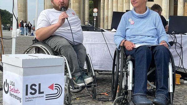 Die beiden Rollstuhlfahrer Alexander Ahrens, hier mit Mikrofon, und Sigrid Arnade vor einer nachgebauten Wahlurne am Brandenburger Tor.