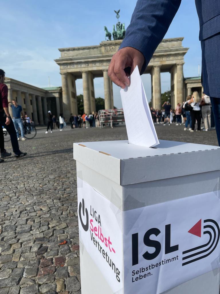 Ein Mann wirft einen Stimmzettel in eine symbolisch vor dem Brandenburger Tor aufgestellte Wahlurne.