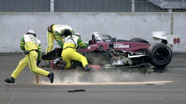 Drei Helfer in gelben Anzügen sind zum brennenden Rennwagen des Italieners Alessandro Zanardi gerannt.