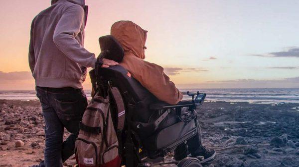 Mann im E-Rollstuhl mit Assistenz am Meer