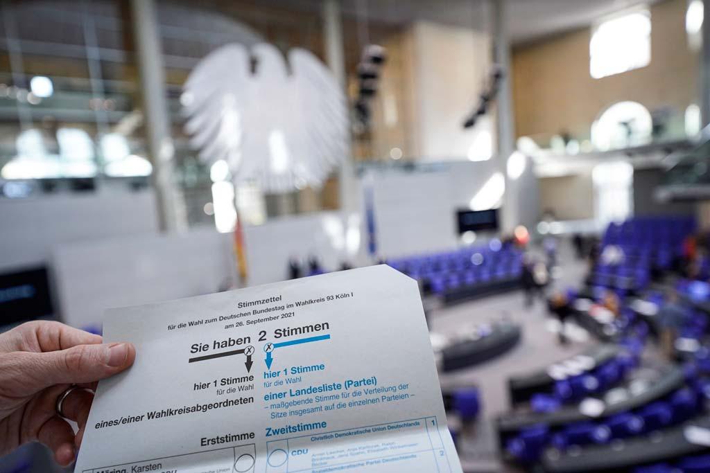 Stimmzettel zur Bundestagswahl mit dem Plenarsaal im Hintergrund