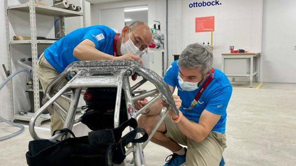 Zwei Mitarbeiter von Ottobock reparieren einen Rollstuhl.