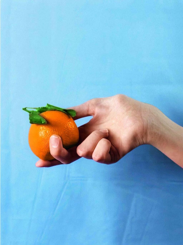 Hand hält Orange vor hellblauem Hintergrund