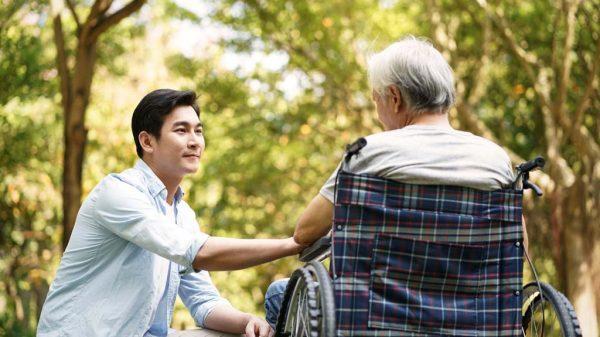 Junger Mann betreut alten Mann im Rollstuhl.