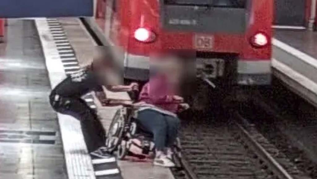 Hermann hält den Rollstuhl am Bahnsteig fest