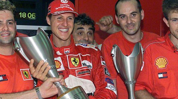 Michael Schumacher hält einen Pokal.