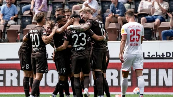 Spieler des St. Paulis in braunen Trikots beglückwunschen sich gegenseitig, während rechts ein Gegenspieler offensicht bedrückt den Rücken zur Kamera gedreht hat.