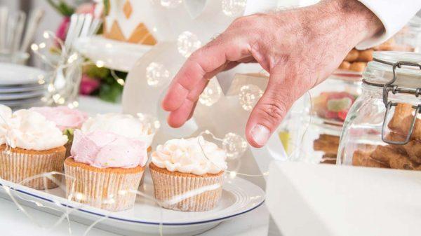 Mann greift nach einem Cupcake.
