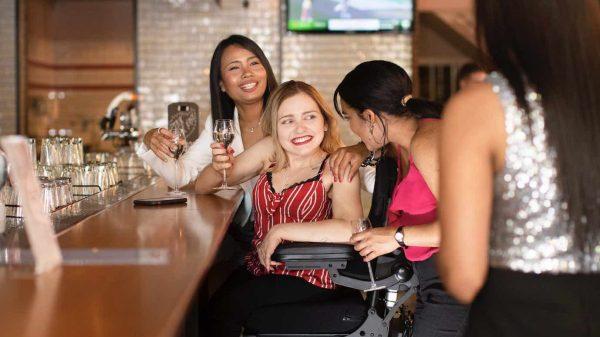 Eine lachende Frau im elektrischen Rollstuhl in einer Gruppe mit drei anderen Frauen.