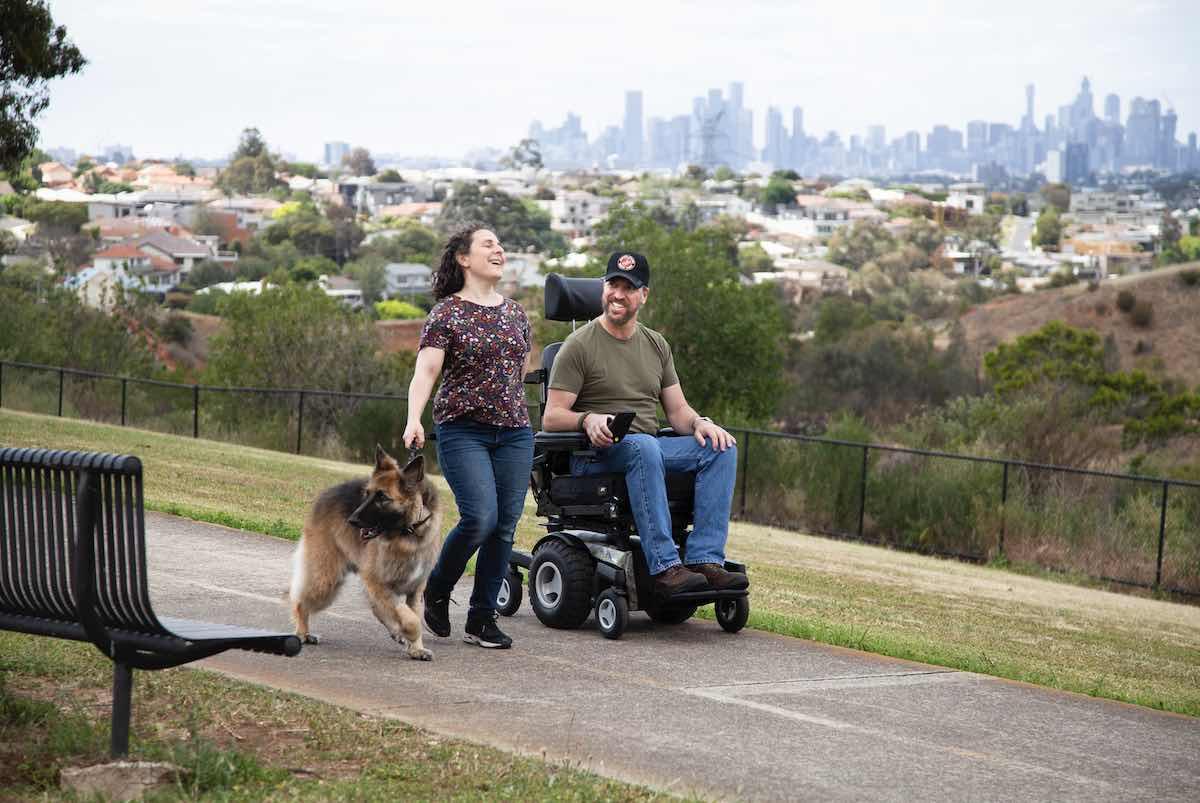 Ein Mann im Rollstuhl, seine Begleiterin und ein Hund gehen spazieren