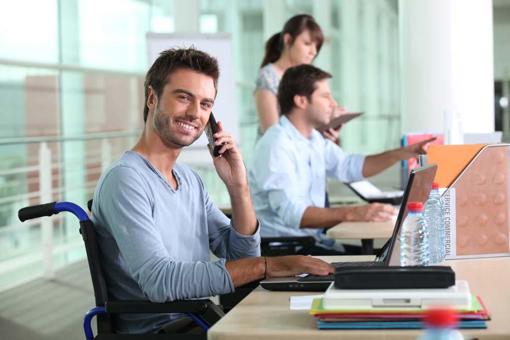 Mann mit Rollstuhl an seinem Arbeitsplatz im Büro.